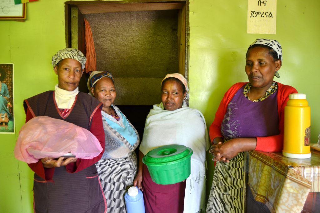 Maedotin osuuskunnan naisia toimittamassa kahvia ja paikallisia munkkeja tilaukseen.